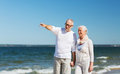 Happy senior couple walking on summer beach Royalty Free Stock Photo