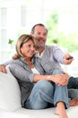 Happy senior couple watching tv television at home Stock Photos