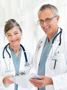 Happy senior doctors standing together with report Royalty Free Stock Images