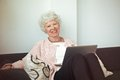 Happy senior lady at home with laptop woman sitting on the couch Royalty Free Stock Photo