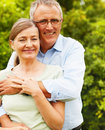 Happy senior man embracing his wife at the park Stock Photography