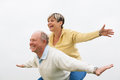 Happy senior man giving piggyback to woman couple together with arms outstretched Royalty Free Stock Photos