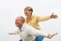 Happy senior man giving piggyback to woman