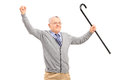 A happy senior man holding a cane and gesturing happiness isolated on white background Royalty Free Stock Photos