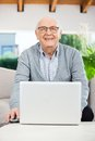 Happy senior man with laptop at nursing home porch portrait of sitting on couch Stock Photo