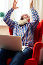 Happy senior man with laptop raising his hands up and screaming Stock Photo