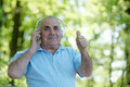 Happy senior man listening to music on his headphones as he relaxes in the garden giving a thumbs up of approval with a big smile Stock Images