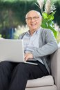 Happy senior man sitting with laptop on couch portrait of at nursing home porch Royalty Free Stock Photos