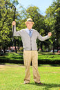 Happy senior man standing and gesturing happiness in park full length portrait of a Stock Image