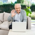 Happy senior man video chatting on laptop waving while at nursing home porch Royalty Free Stock Images