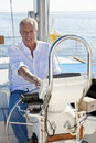 Happy Senior Man At The Wheel of a Sail Boat Royalty Free Stock Photography