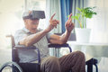 Happy senior man on wheelchair using VR headset