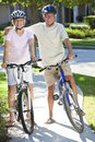 Happy Senior Man & Woman Couple on Bicycles Stock Photo