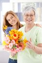 Happy senior mother with flowers at mother s day and daughter smiling holding Stock Photography