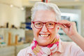 Happy senior with new glasses at woman optician retail store Stock Photo