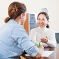 Happy senior woman answer questions women of social worker in home Royalty Free Stock Photos