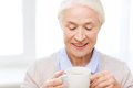 Happy senior woman with cup of tea or coffee age drink and people concept smiling at home Stock Photography
