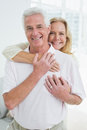 Happy senior woman embracing man from behind portrait of a women men at home Royalty Free Stock Image