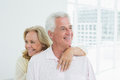 Happy senior woman embracing man from behind portrait of a women men at home Royalty Free Stock Images
