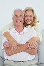 Happy senior woman embracing man from behind portrait of a women men at home Stock Photos