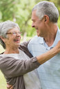 Happy senior woman embracing man at park Stock Image