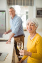 Happy senior woman holding glass of wine in kitchen Royalty Free Stock Photo