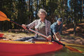 Happy senior woman in a kayak at the lake portrait of women holding paddles canoeing with men background Royalty Free Stock Photo