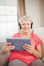 Happy senior woman listening to music portrait of on digital tablet Royalty Free Stock Photography