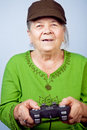 Happy senior woman playing video games Stock Images