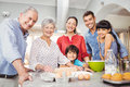 Happy senior woman preparing food with family portrait of women at home Royalty Free Stock Image