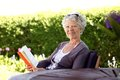Happy senior woman reading book in the garden with hand sitting her backyard looking at camera smiling elder novel Stock Photography