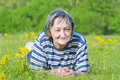 Happy senior woman relaxing on the grass on a sunny afternoon Stock Photography
