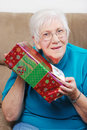 Happy senior woman shaking her christmas present Royalty Free Stock Photos