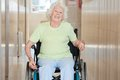 Happy senior woman sitting in a wheel chair at hospital corridor Stock Photos