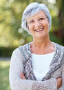 Happy senior woman standing with folded hand Royalty Free Stock Photos