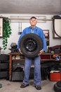 Happy senior worker changing tire in garage Royalty Free Stock Photo