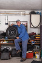 Happy senior worker with a tire in garage Royalty Free Stock Photo