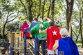 Happy seniors wearing superhero costumes at a playground Royalty Free Stock Photo