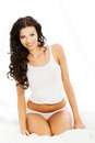 Happy sensual young woman sittng in bed sitting and smiling to camera Royalty Free Stock Photography