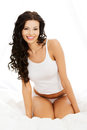 Happy sensual young woman sittng in bed sitting and smiling to camera Royalty Free Stock Photo