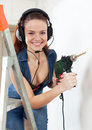 Happy sexual girl in headphones with drill portrait of interior Stock Photography