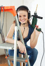Happy sexy girl in overalls with drill makes repairs at home Stock Images