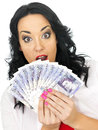 Happy shocked attractive young woman holding money with long black curly hair and hispanic or european features looking at the Royalty Free Stock Photography