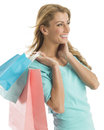 Happy shopaholic woman looking away while carrying shopping bags young against white background Stock Photos