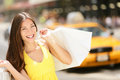 Happy shopper holding shopping bags new york city woman manhattan usa beautiful fresh joyful female model walking in street in Royalty Free Stock Image