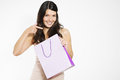 Happy shopper pointing to her shopping bag with a playful conspiratorial look as she smiles in contentment at the purchase of a Royalty Free Stock Images