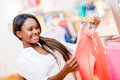 Happy shopping woman looking at clothes at a retail store Royalty Free Stock Image