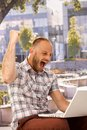 Happy shout outdoors young man using laptop shouting with clenched fist Royalty Free Stock Photos