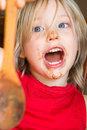 Happy shouting child holding chocolate covered wooden spoon Royalty Free Stock Photo