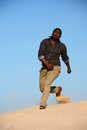 Happy singing black man full body of an african american young and running down the dunes in front blue sky background Royalty Free Stock Photo